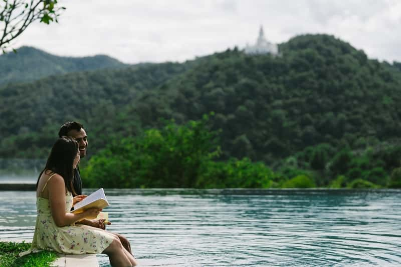 Couple Reading Books while on a beautiful landscape - Travel