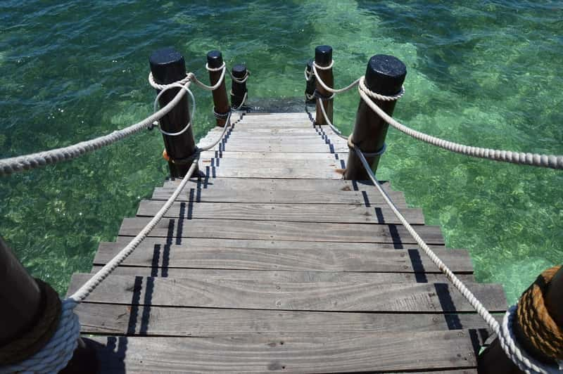 wooden stairs in the sea - travel to exotic destinations with the cheapest flights