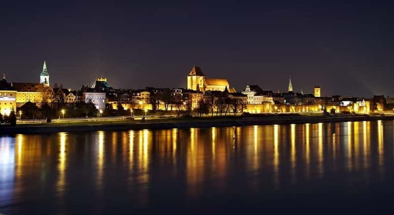 Beautiful city of Torun behind the River late night. Lights reflect on the River. Visit Torun from Warsaw. Torun city tours from Warsaw