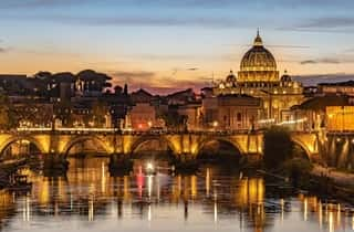 Beautiful view of Rome behind the Tyber River during the night with lights reflection