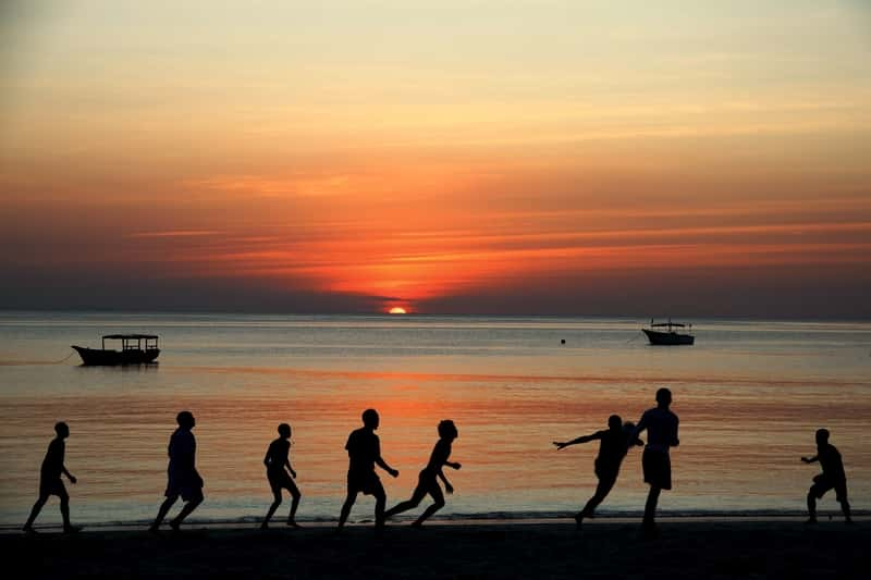 People playing football on the beach -  Sunrise in Tanzania